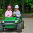 Funny sisters go to little green toy car — Stock Photo