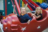 Funny sisters on carousel ride — Stockfoto