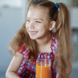 Little girl, which sits on table and drinking juice — Stock Photo #13396240