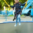 Happy little girl jumping on trampoline — Stock Photo