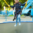 Happy little girl jumping on trampoline - Stock Photo