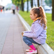 Little girl in jacket sitting on paving-stone curb — Stock Photo #13396244