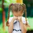 Little girl with pigtails crying - Stock Photo