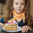 Little girl eating cake - Stock Photo