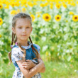 Beautiful smiling little girl on sunflower field — Stock Photo