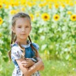 Beautiful smiling little girl on sunflower field — Stock Photo #13396255