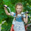 Beautiful smiling little girl with children's bicycle — Stock Photo #13396274