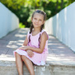 Little girl with pigtails sitting on stone step — Stock Photo #13396279