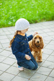 Ittle girl in denim suit with brown dog — Stock Photo
