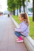 Little girl in jacket sitting on paving-stone curb — Stock Photo