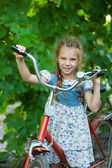 Beautiful smiling little girl with children's bicycle — Stock Photo