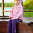 Little girl in pink jacket sitting on wooden bench — Stock Photo #13431221