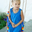 Little girl on swing in children's city park - Stock Photo