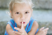 Ittle girl puts her finger to mouth — Stock Photo