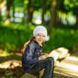 Little girl in denim suit sitting on wooden railing — Stock Photo #13523479