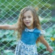Smiling little girl with curly hair near fence of grid - Stock Photo