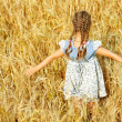 Little girl on field with ripe wheat eared — Stock Photo