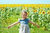 Schöne lächelnd mädchen am sonnenblumenfeld — Stockfoto