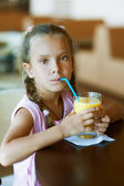 Little girl with pigtails drinking orange juice — Stock Photo