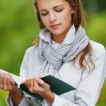 Beautiful woman reading green book — Stock Photo #13535851