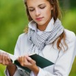Beautiful woman reading green book — Stock Photo