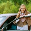 Stock Photo: Smiling beautiful young woman-driver near car