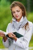 Beautiful woman reading green book — Stock Photo