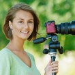 Smiling beautiful young woman with camera - Stockfoto