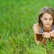 Young woman-student reading book on grass — Stock Photo #13632320