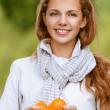 Beautiful woman holding few juicy oranges — Stock Photo