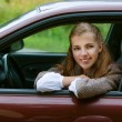 Smiling beautiful young woman-driver in car — Stock Photo #13638567