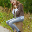 Sad beautiful young woman sitting on road suitcase — ストック写真