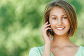 Smiling beautiful young woman with phone — Stock Photo