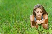 Młoda kobieta uczeń czytanie książki na trawie — Zdjęcie stockowe