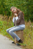 Sad beautiful young woman sitting on road suitcase — Stock fotografie