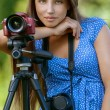 Calm young woman with camera on tripod - Foto Stock