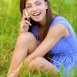 Stock Photo: Womsitting on grass and talking on phone