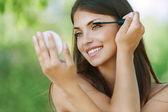 Donkerharige lachende jonge vrouw kleurstoffen haar wimpers — Stockfoto