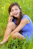 Woman sitting on grass and talking on phone — Stock Photo