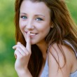 Young woman close-up puts finger to her lips — Stock Photo #13860823