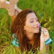 Young woman lying on grass and smelling flower — Stock Photo