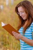 Libro de lectura naranja mujer joven — Foto de Stock