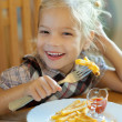 Little girl eating French fries — Stock Photo #14158513