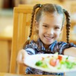 Stock Photo: Smiling girl holds out plate of delicious food