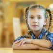 Beautiful girl with pigtails sitting on wooden desk — Stock Photo #14183954