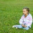 Royalty-Free Stock Photo: Beautiful girl with pigtails sitting on green grass