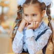 Sad girl with beautiful bows sitting at wooden table — Stock Photo