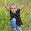 Beautiful girl climbing on a metal grid — Stock Photo