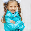 Stock Photo: Smiling beautiful girl with bows in blue cloak