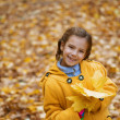 Beautiful girl in yellow coat holding maple leaf — Stock Photo